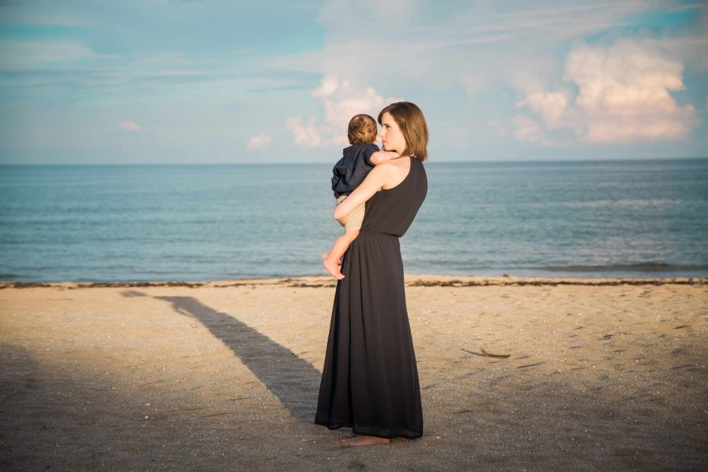 Rebekah holding her son at the beach